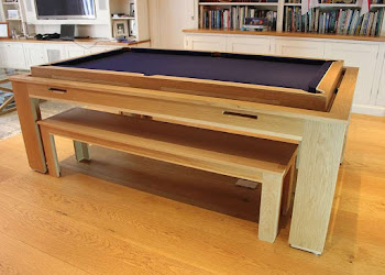 the spartan pool table with the top elevated with blue felt on a light wood flooring