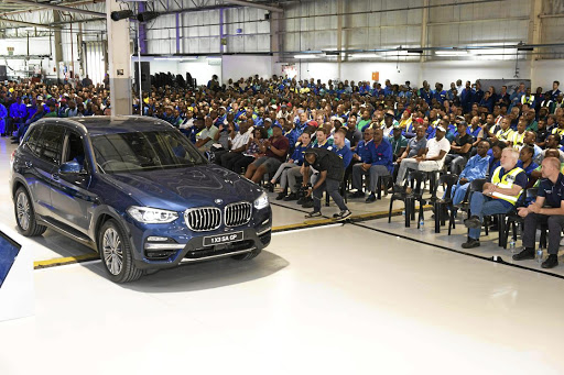 The first BMW X3 built in SA rolls off the company's production line in front of employees.  Picture: BMW