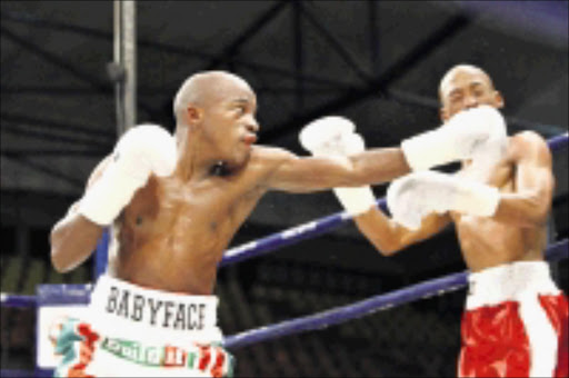 ONE WAY: SA Champion, Moruti Mthalane, left, lands a punch on Lehlohonolo Ramagole during their national flyweight title fight in North West. 19/04/09. Pic. Antonio Muchave. © Sowetan.