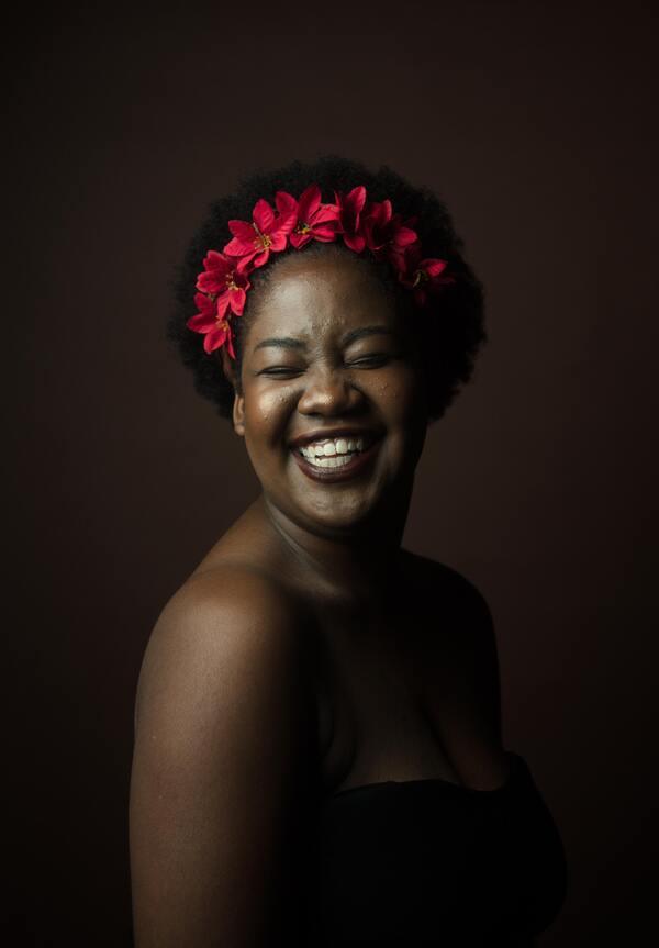 Mulher negra com uma coroa de flores na cabeça posando e sorrindo para a foto.