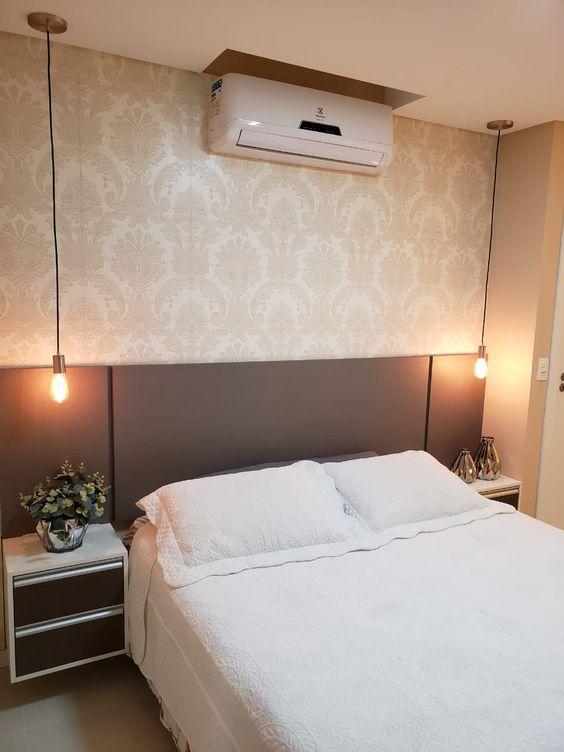 Quarto com cama de casal com cabeceira de MDF cinza, parede de fundo com papel de parede em tom neutro e lâmpadas pendentes.