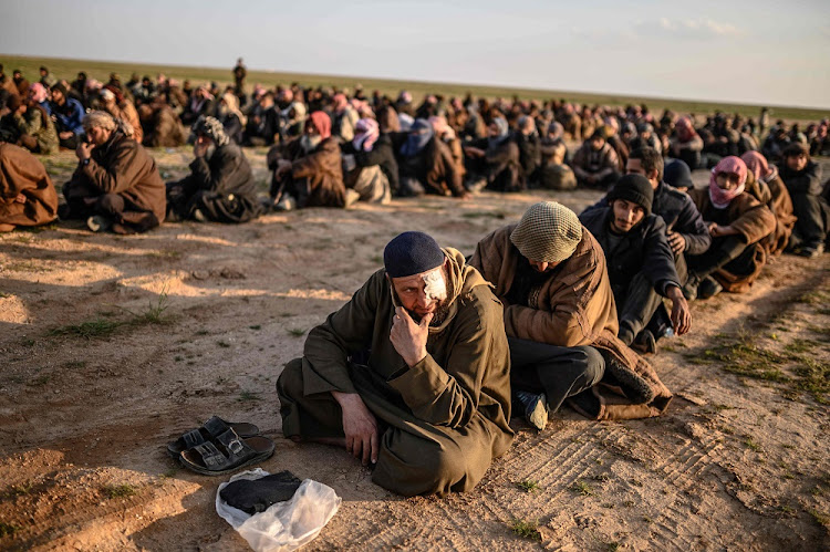 Men suspected of being Islamic State fighters wait to be searched by members of the Syrian Democratic Forces after leaving the group's last redoubt of Baghouz, in Syria's northern Deir Ezzor province, February 22 2019. Picture: AFP/BULENT KILIC