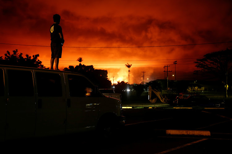 Darryl Sumiki of Hilo watches lava light up the sky during the ongoing eruptions of the Kilauea Volcano in Hawaii.