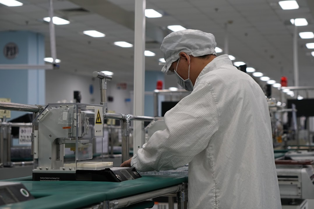 A factory worker concentrating on a task at their station, wearing a checkered factory uniform, cap and mask.