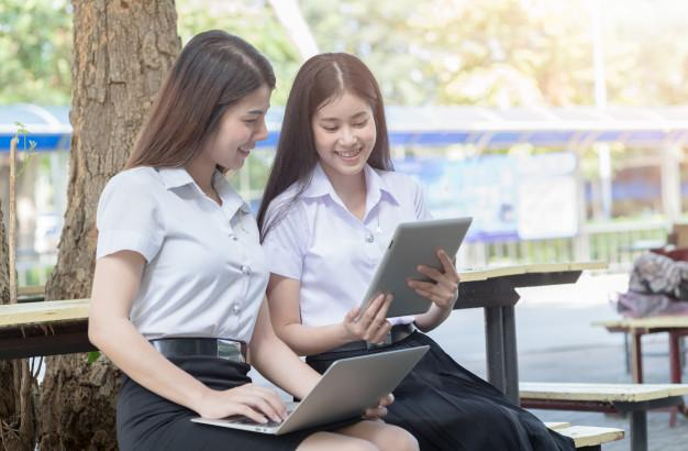 Two young woman student play tablet and laptop on chair in university, education concept Premium Photo