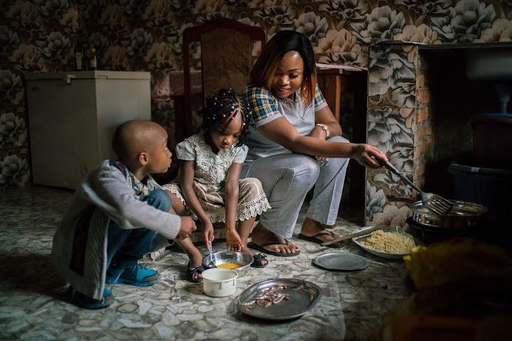 Riziki fazendo café da manhã com dois de seus filhos.