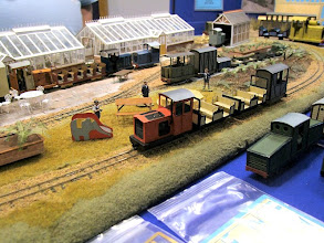 Photo: 007 A modern image diesel loc passes through the frontage of the Minimum Gauge Models layout with a train of two Bassett Lowke 8 seater coaches and a freelance brakevan. Ravenglass loco ICL1 in the foreground and a Rhyl Miniature Railway 10 seater open coach just in front of the greenhouses.