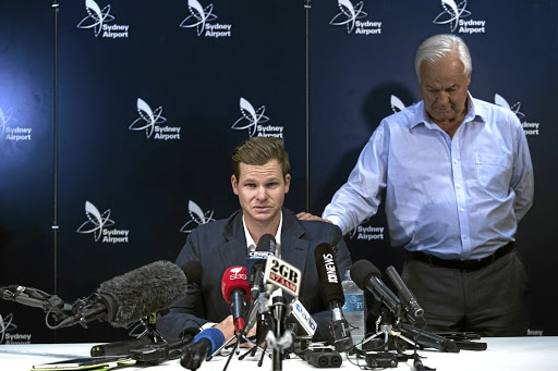 An emotional Steve Smith is comforted by his father, Peter, as he faces the media at Sydney International Airport on Thursday after flying back to Australia amid the ball-tampering scandal in South Africa. Picture: Getty Images