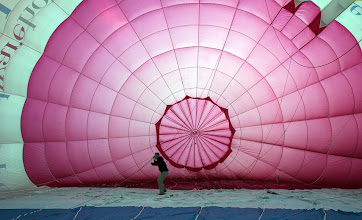 Photo: BRISTOL, ENGLAND - AUGUST 06:  A balloonist prepares a balloon for flying as hot air balloons prepare to take to the skies over Bristol city centre to launch the Bristol International Balloon Fiesta on August 6, 2012 in Bristol, England. The early morning flight of over twenty balloons over the city was organised as a curtain raiser for the four-day Bristol International Balloon Fiesta which starts on Thursday. Now in its 34th year, the Bristol International Balloon Fiesta is Europe's largest annual hot air balloon event in the city that is seen by many balloonists as the home of modern ballooning.  (Photo by Matt Cardy/Getty Images)
