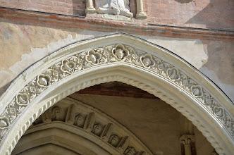 Photo: Arco inferiore a sesto acuto, ornato con motivi floreali intervallati da testine femminili e uccelli rapaci