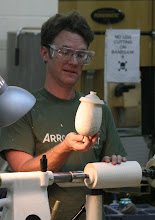 "Photo: Mark makes every form by eye so they are subtly different and unique -- he does not use a ""story stick"". Here, he describes the features of the shape and how they will be marked on the raw cylinder."