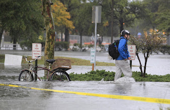 Photo: A Norfolk resident chains his bike and heads to work in flood waters near downtown in Norfolk, Virginia.