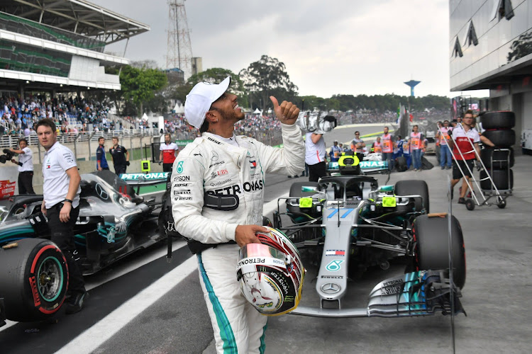 Mercedes' British driver Lewis Hamilton celebrates after taking the pole position for the F1 Brazil Grand Prix in the qualifying session at the Interlagos racetrack in Sao Paulo, Brazil on November 10, 2018.