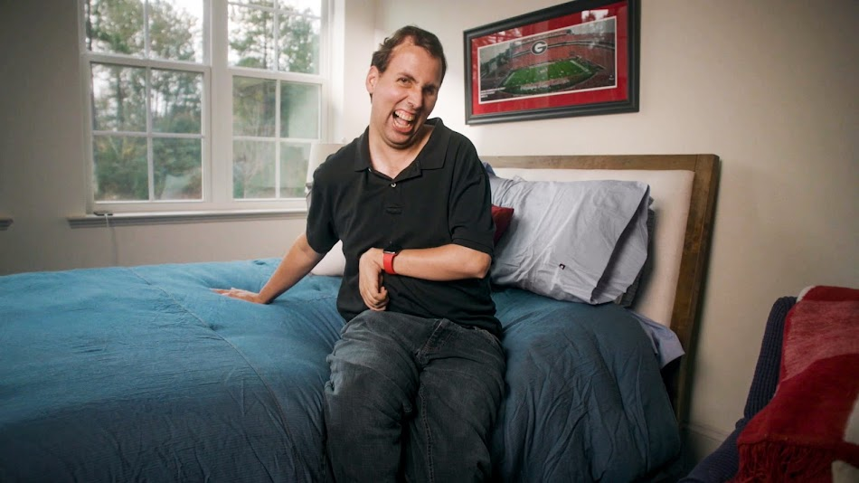 Person in black collared shirt sitting on bed smiling in front of a window.