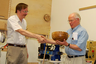 "Photo: Gary Guenther presents the Liam O'Neill demo bowl to Phil Brown for donating the original curly-elm blank and for bringing ""tons"" of wood to MCW Silent Auctions.  Liam turned the bowl at our meeting a year ago; Gary dried it successfully and recently completed and finished it.  Liam will sign it when he is in the area next April."