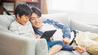 young boy and man look at tablet together