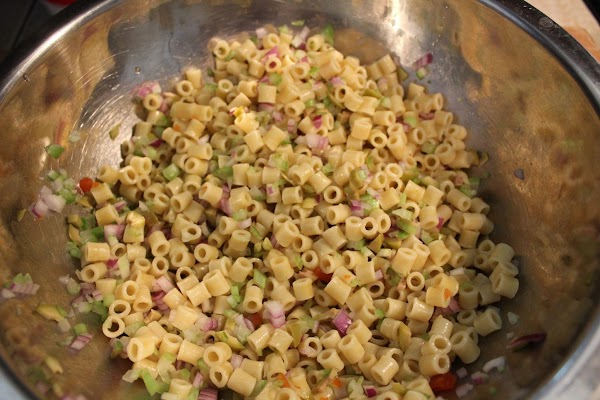 Adding onion, celery and green olives to pasta.