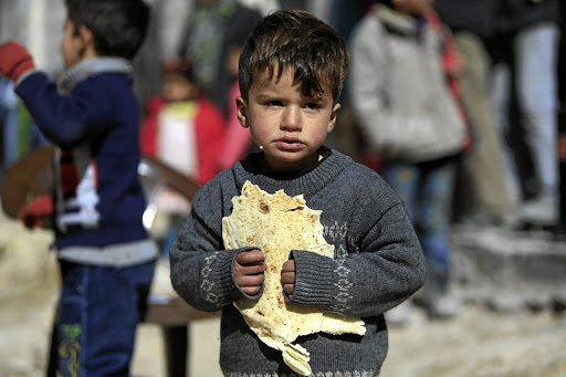 Homeless: A displaced boy carries bread at a shelter in Jibreen, on the outskirts of Aleppo, Syria, on Wednesday. Picture: REUTERS