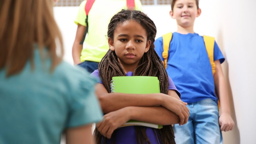 little girl with green notebook upset at school