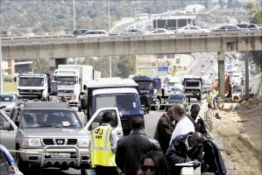 CHAOS: Traffic cameto a standstill when 15 menallegedly ambushed a cash van on the M1North near the Rivonia off-ramp yesterday. Pic. Antonio Muchave. 28/04/2010. © Sowetan.