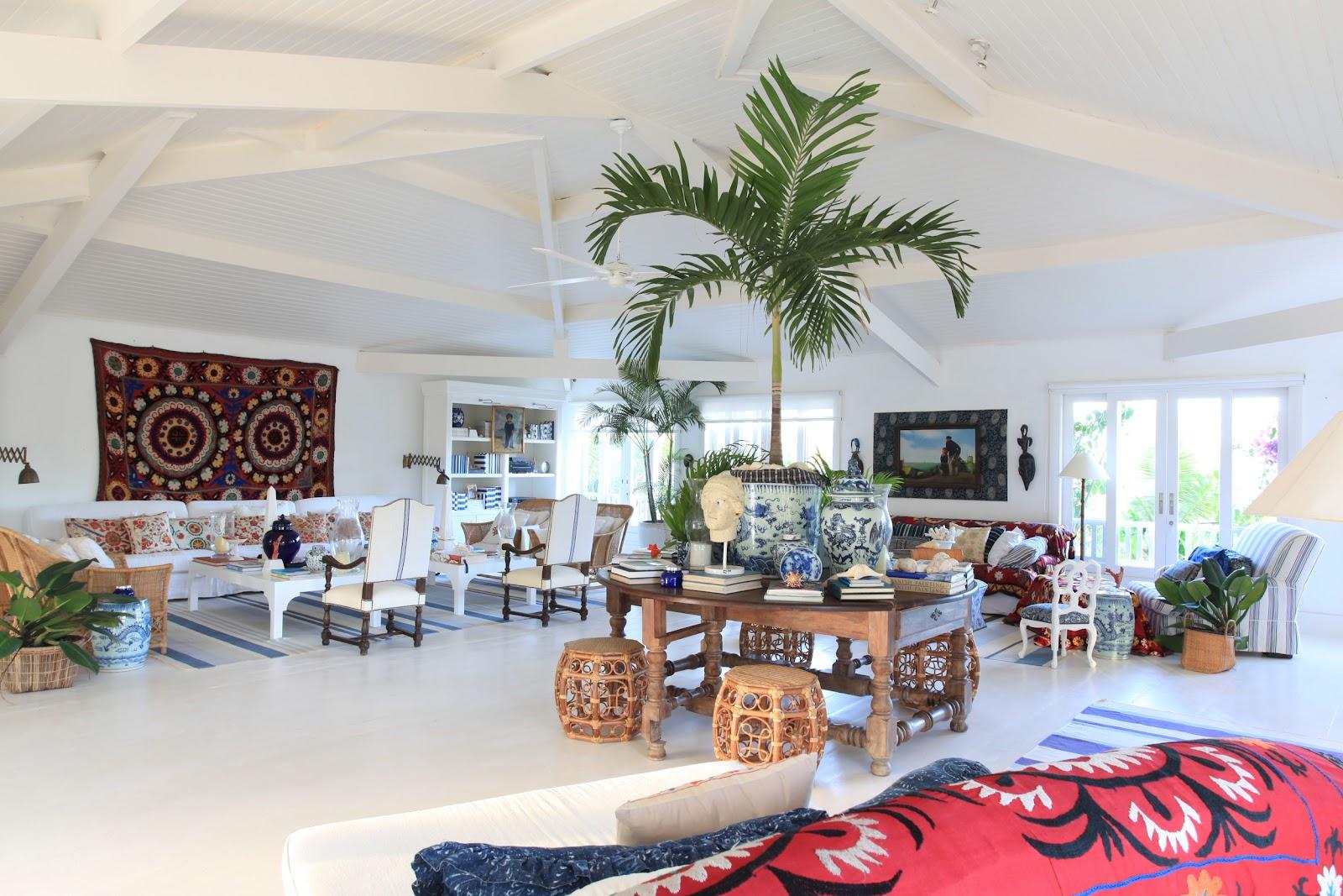 Ambiente branco, com mesas de madeira e bancos, plantas e quadros, sofás e poltronas.
