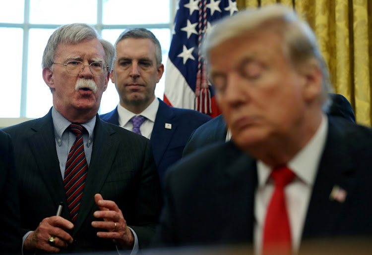 Donald Trump listens to his then national security adviser John Bolton in 2019. Picture: REUTERS/LEAH MILLIS
