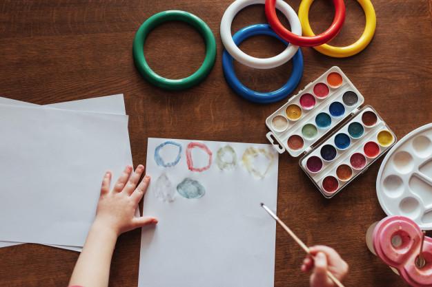 Foto com vista de cima de uma mesa, na qual uma criança está realizando pinturas com tinta aquarela em uma folha de sulfite.