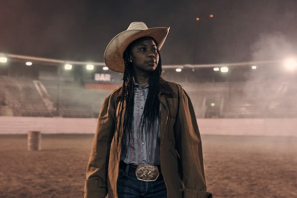 Keiara gazing across a brightly lit arena at night in her rodeo garb.