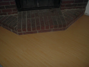 Photo: hardwood flooring under cut at fireplace, no molding needed.