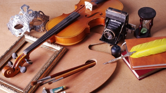 an empty frame, a violin, a few paintbrushes, a camera, and hourglass, a feather quill, a few books, and other items perfect for the creative individual.