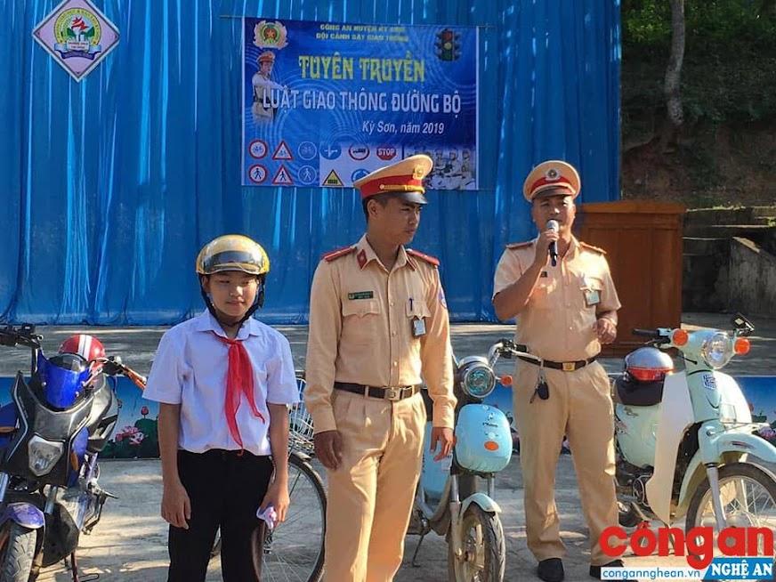 Cán bộ Đội CSGT Công an huyện Kỳ Sơn hướng dẫn cách đội mũ bảo hiểm đúng quy định cho các em học sinh