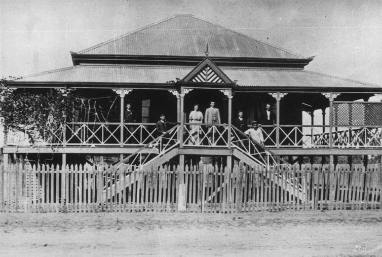 House in Emerald, Queenland with a short-ridged roof and a generous wraparound veranda, probably built between 1880s and 1890s. This home features acroteria on the edges of the roof and veranda, and carved veranda posts. John Oxley Library, State Library of Queensland