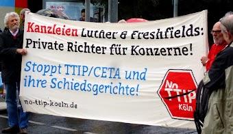 Demonstranten mit Transparent: »Kanzleien Luther & Freshfields: Private Richter für Konzerne! Stoppt TTIP/CETA und ihre Schiedsgerichte! no-ttip-koeln.de«.
