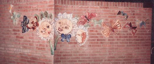Photo: Reliëf voor kinderopvang en -verblijf voor gehandicapte (dove?) kinderen, Stichting Pameyer, om een hoek met bloemen en vlinders, 1979. afgebeeld bloemen met gezichten en vlinders rond hoek van bakstenen muur