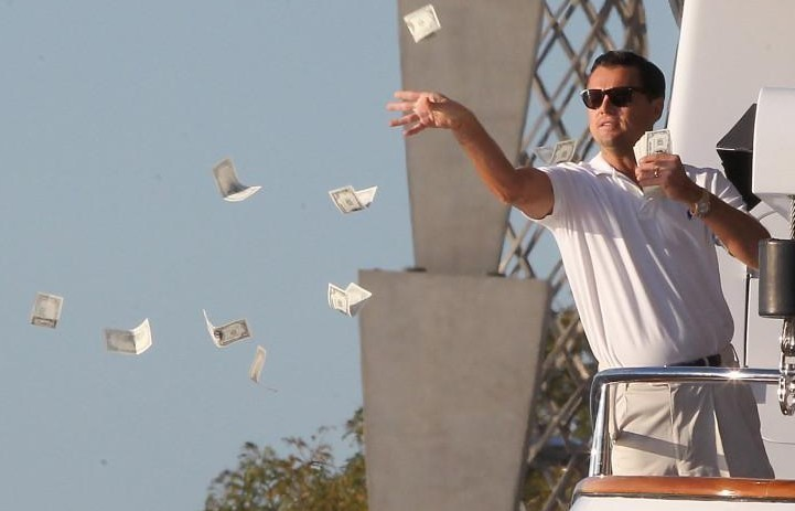 A man in a white polo shirt throwing a handful of money.