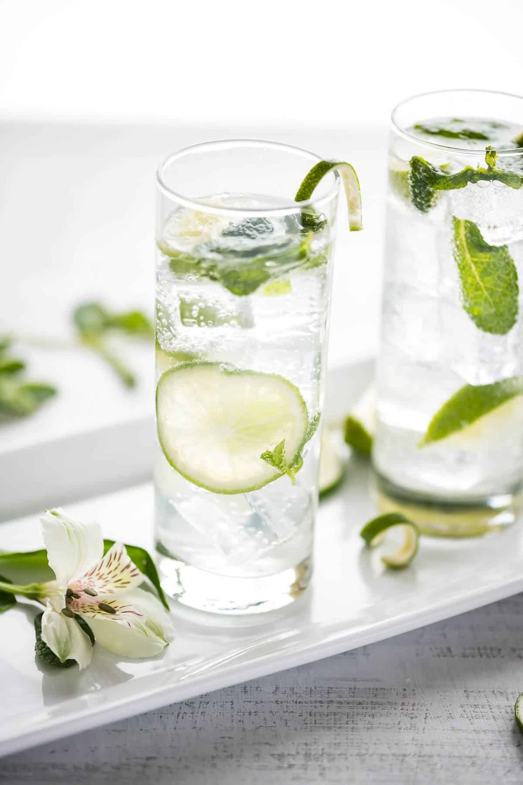 2 mojito mocktails in tall glasses with mint & lime on white tray with white flower