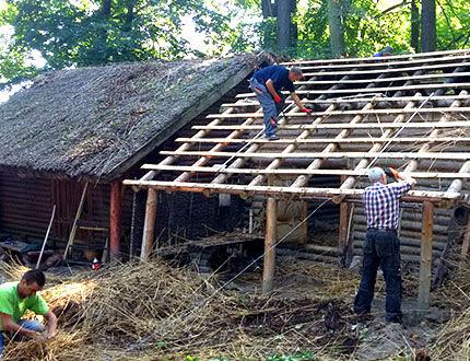 Robotnicy na dachu układają deski