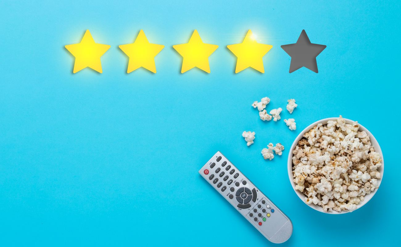 Bowl of popcorn and a remote from the TV set on a blue background. Rating four stars out of five