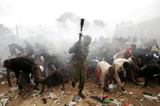 CHAOS Police fire teargas to control Kenyans trying to force their way into the inauguration of President Uhuru Kenyatta in Nairobi on Tuesday