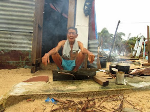 Photo: A man cooks his family's meal outside because their home was among the totally destroyed