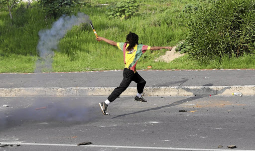 SOS: A protester launches a signal flare, stolen from Hout Bay harbour, at riot police. Ferry operator Ken Evans described the violence as 'the most serious and disturbing incident we've had in Hout Bay'.