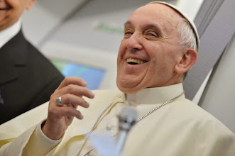 """Photo: Pope Francis smiles as he answers reporters questions during a news conference aboard the papal flight on the journey back from Brazil, Monday, July 29, 2013. Pope Francis reached out to gays on Monday, saying he wouldn't judge priests for their sexual orientation in a remarkably open and wide-ranging news conference as he returned from his first foreign trip. """"If someone is gay and he searches for the Lord and has good will, who am I to judge?"""" Francis asked. His predecessor, Pope Benedict XVI, signed a document in 2005 that said men with deep-rooted homosexual tendencies should not be priests. Francis was much more conciliatory, saying gay clergymen should be forgiven and their sins forgotten. Francis' remarks came Monday during a plane journey back to the Vatican from his first foreign trip in Brazil. (AP Photo/Luca Zennaro, Pool)"""