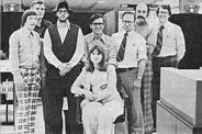 Photo: Computing Services System Programming Group, c. 1974. l to r: John Stasiuk, Daryl Webster, Grant Crawford, Alan Davis, Kathryn Ward (sitting), Gary Jackson, Rolly Noel, and Gerry Gabel. Not pictured is Charlie Benet.