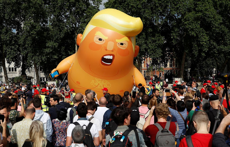 Onlookers stand in front of a blimp portraying U.S. President Donald Trump, in Parliament Square, during the visit by Trump and First Lady Melania Trump in London, Britain July 13, 2018.