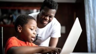 imagen de un hombre mirando a un niño escribir