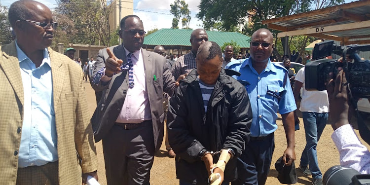 Naftali Kinuthia is escorted outside the Eldoret High Court by police officers on Monday, April 15, 2019.