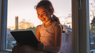 young girl smiling at tablet screen