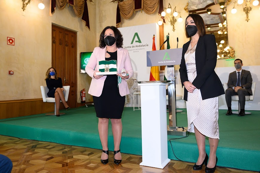 María del Mar Ayala, presidenta del Colegio de Graduados Sociales recogiendo la bandera