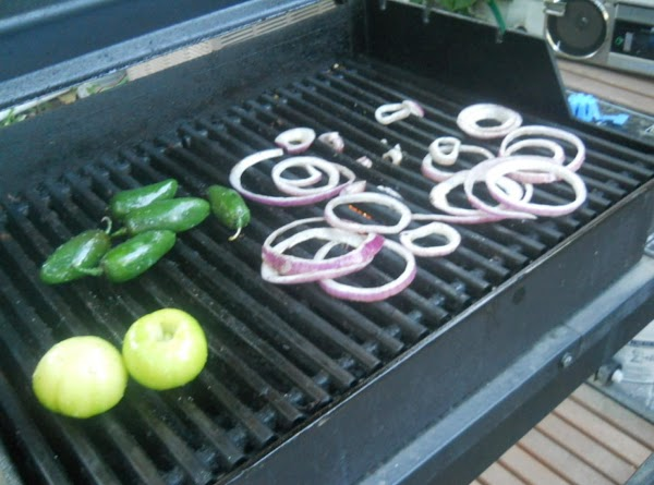 Toss tomatillos and red onion slices with olive oil and kosher salt, place on...