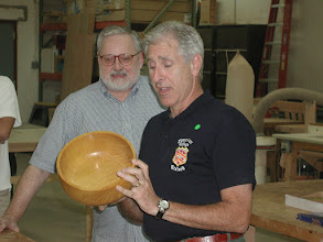 Photo: Denis Zegar discusses his osage orange bowl as Michael Blake looks on.